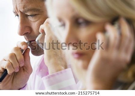 Business colleagues using mobile phones, focus on man in background, side view - stock photo