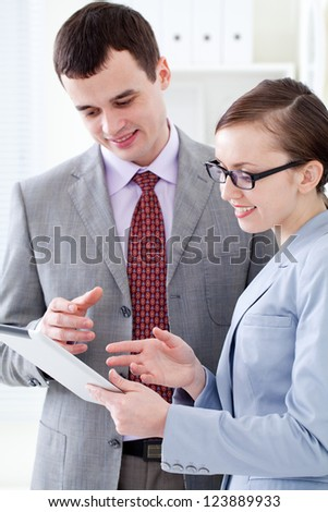 Business colleagues working and holding a digital tablet