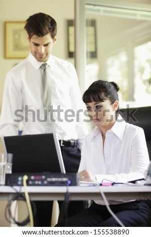 Business colleagues working on laptop in office. Shallow focus. - stock photo