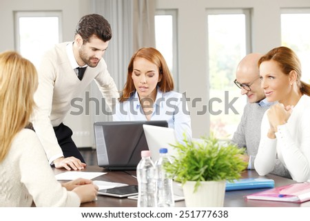 Business colleagues working on laptop while they sitting at meeting. Teamwork at office.  - stock photo