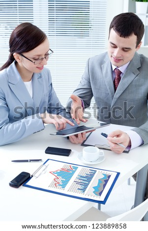 Business colleagues working together and using a digital tablet