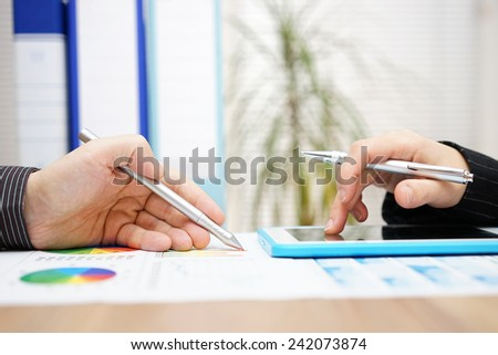 Business colleagues working together on project with tablet computer and paper report - stock photo
