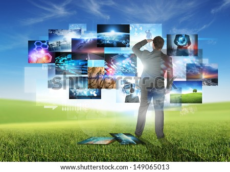 Business Communication - A businessman looking at floating media images.