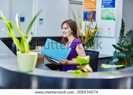 Business, communication and call center concept - beautiful young receptionist at work - stock photo