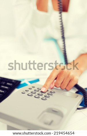 business, communication and helpline concept - businesswoman with phone calling or dialing the number - stock photo