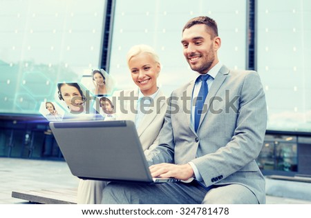 business, communication, technology and people concept - smiling businesspeople making video call or conference with laptop computer on city street - stock photo