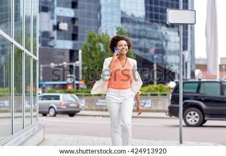 business, communication, technology and people concept - young smiling african american businesswoman calling on smartphone in city - stock photo