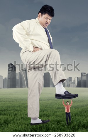 Business competition concept with big businessman trample a little entrepreneur - stock photo