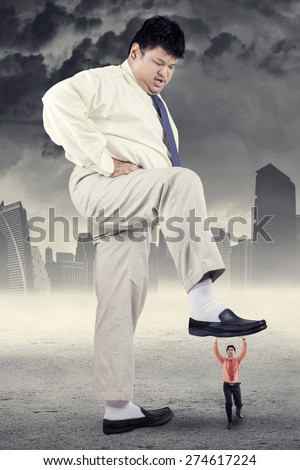 Business competition concept with big businessman treading little entrepreneur - stock photo