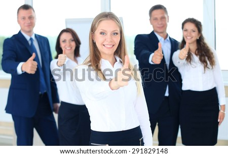 business concept - attractive businesswoman with team in office showing thumbs up - stock photo