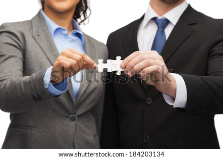 business concept - businessman and businesswoman holding puzzle pieces in office - stock photo
