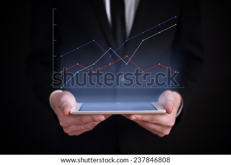 business concept. businessman holding a tablet with the projection of the graph above the screen. financial growth. - stock photo