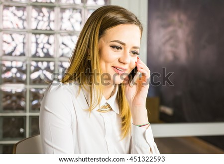 business concept - businesswoman talking on the phone in office