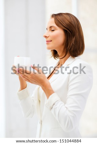 business concept - businesswoman with cup of coffee in office