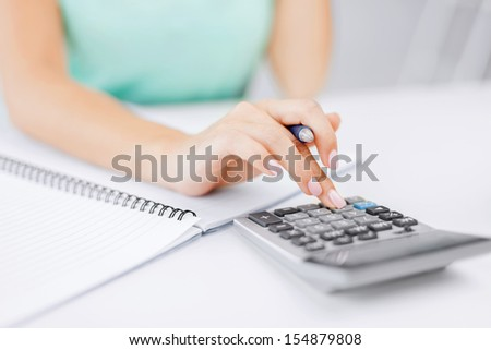business concept - businesswoman working with calculator in office - stock photo