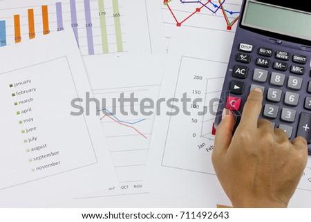 business concept : calculator with hand on stock market report as background