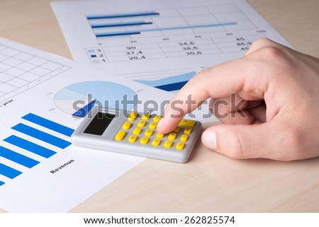 business concept - close up of graphs, charts and male hand with calculator - stock photo