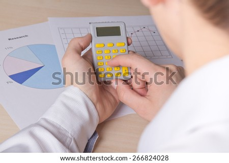 business concept - close up of male hands accounting something with calculator