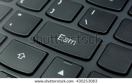 Business Concept: Close-up the Earn button on the keyboard and have Black color button isolate black keyboard