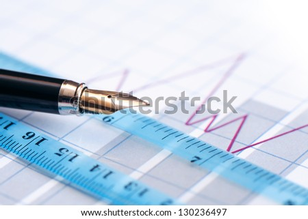 Business concept. Closeup of fountain pen near ruler on paper background with business chart