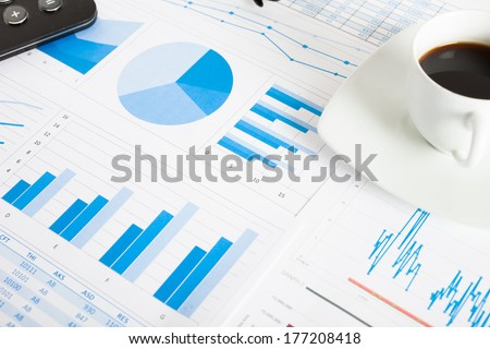Business concept: coffee and a calculator over financial documents - stock photo