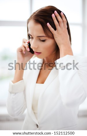 business concept - confused woman with smartphone in office - stock photo
