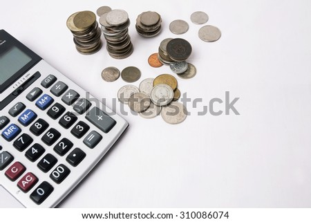 Business concept.  Counting money on calculator, stack of coins. Financial Accounting - money and calculator.