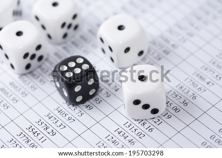Business concept. Dice play on paper background with table of digits