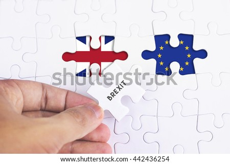 Business Concept - Female hand and missing puzzle with BREXIT WORD EUROPE AND BRITAIN FLAG.