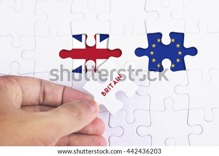 Business Concept - Female hand and missing puzzle with BRITAIN WORD EUROPE AND BRITAIN FLAG.