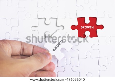Business Concept - Female hand and missing puzzle with BUSINESS AND GROWTH THINKING WORD