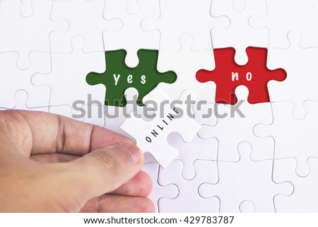 Business Concept - Female hand and missing puzzle with ONLINE, YES and no WORD