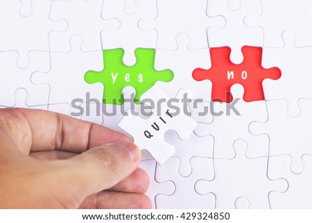 Business Concept - Female hand and missing puzzle with QUIT, YES and no WORD
