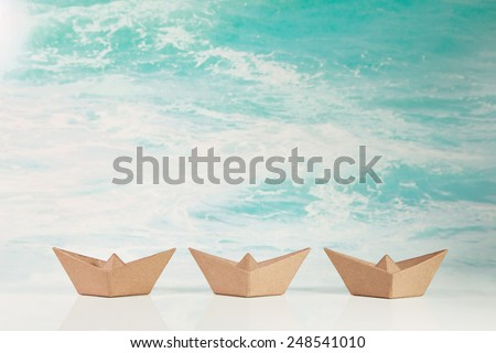 Business concept for challenge and movement: three paper boats on maritime turquoise ocean background. - stock photo