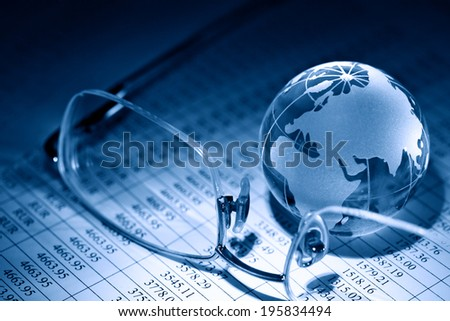 Business concept. Glass globe near spectacles on background with table of numbers - stock photo