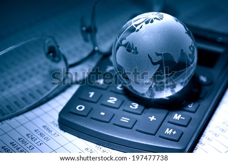 Business concept. Glass globe on calculator near spectacles on background with table of numbers