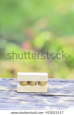 Business Concept - Golden coin stacked with wooden bar on shallow DOF green background.