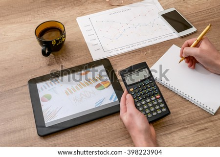 business concept - graph, calculator, tablet and pen on desk - stock photo