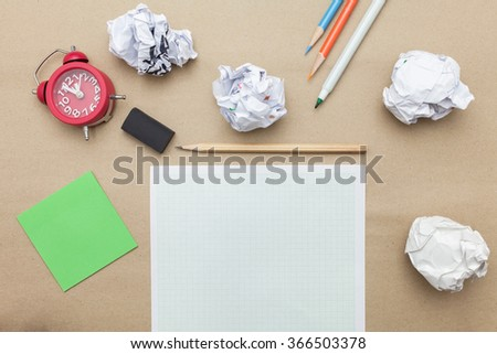 Business concept:Green post it,red clock,white blank paper,crumpled paper and color pencil,pencil,pen on brown paper background - stock photo