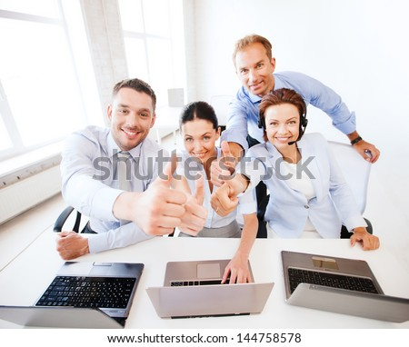 business concept - group of office workers showing thumbs up in call center - stock photo