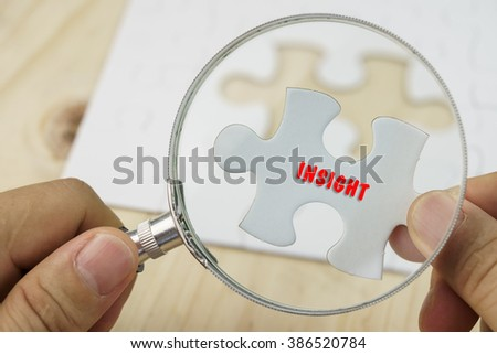 Business concept.Hand with magnifying glass searching for a piece of jigsaw puzzle with INSIGHT word. - stock photo