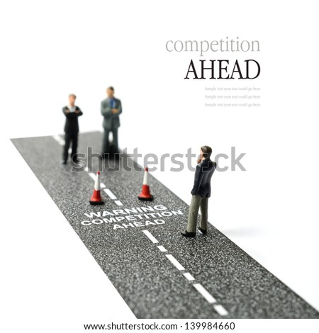 Business concept image depicting competitors waiting ahead. Selective focus on the road text. Copy space. - stock photo