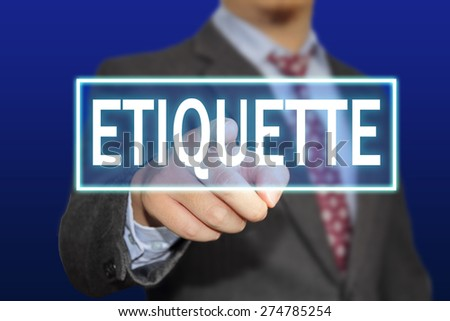 Business concept image of a businessman clicking Etiquette button on virtual screen over blue background - stock photo