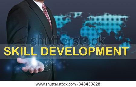 Business concept image of a businessman showing Skill Development words on his hand over blue background with dotted world map - stock photo