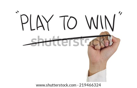 Business concept image of a hand holding marker and write Play to Win isolated on white - stock photo