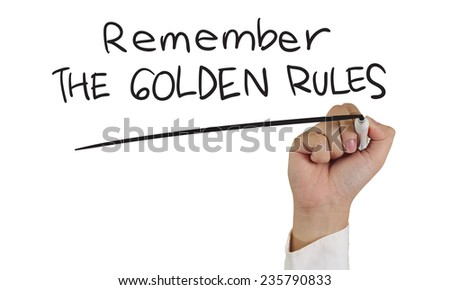 Business concept image of a hand holding marker and write Remember the Golden Rules words isolated on white