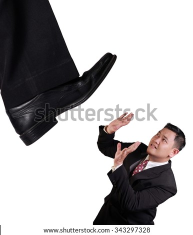 Business concept image of an Asian businessman holding on under pressure of big boss, under giant shoe, isolated on white - stock photo