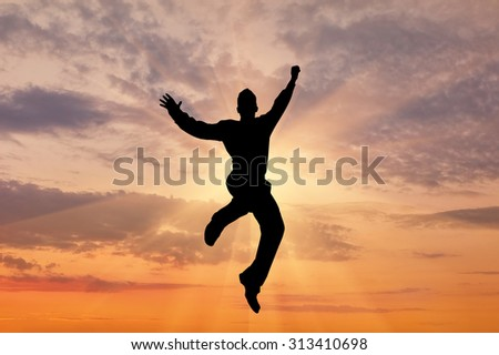 Business concept. In the rays of the sun sky silhouette of a man jumping - stock photo