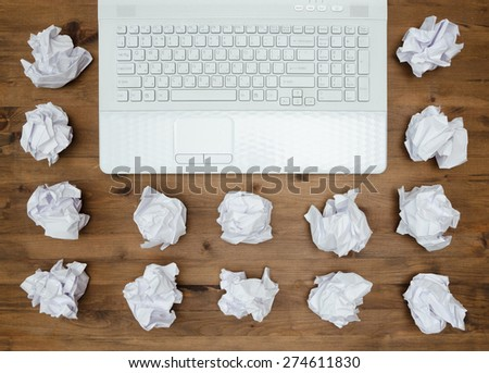 business concept. Laptop, sheets of paper and crumpled wads on table. - stock photo