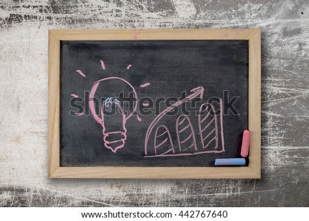 Business concept, Light Bulb icon on Black chalkboard on wooden wall background